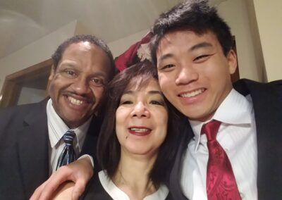 Christian Hall smiling at camera in a family photo with his parents Fe and Gareth.