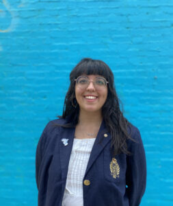Kat Bakarania smiling in front of a blue wall