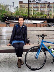 Woman sitting on a bench next to a bike